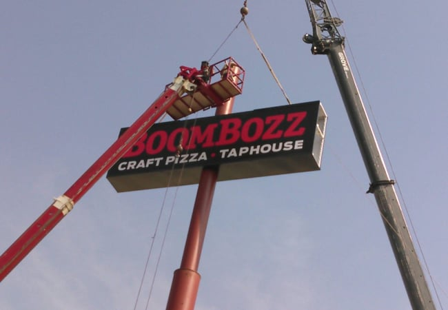 cranes installing BoomBozz sign